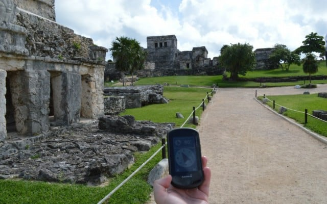 holding a garmin GPS and following the compass in the direction of a geocache at the famous tulum ruins in the yucatan of mexico