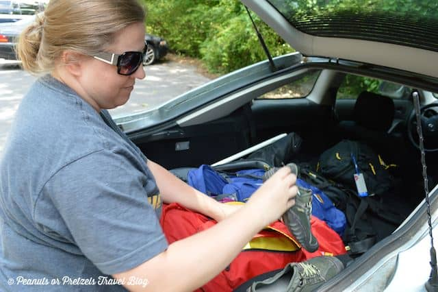 liz with open trunk of car going through bags to unpack shoes for a hike