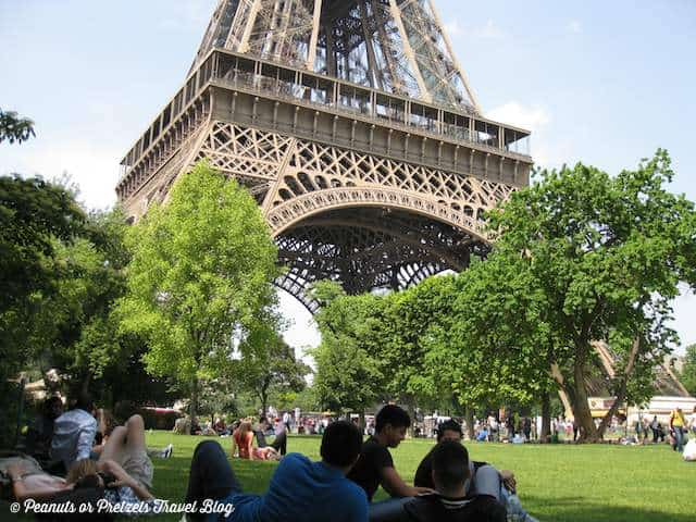 many people picnicking on grass under the Eiffel Tower in Paris on sunny day - a great free thing to do during a vacation