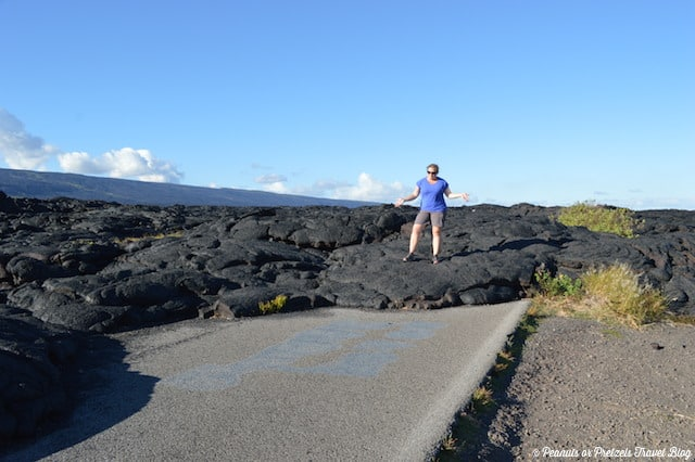 Liz standing on hardened lava rock over a road in Hawaii with comfortable walking shoes with good traction