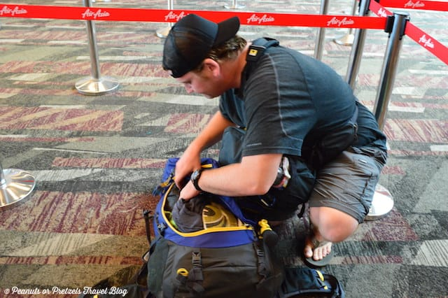 Josh at the airport removing liquids from a bag before checking on the flight