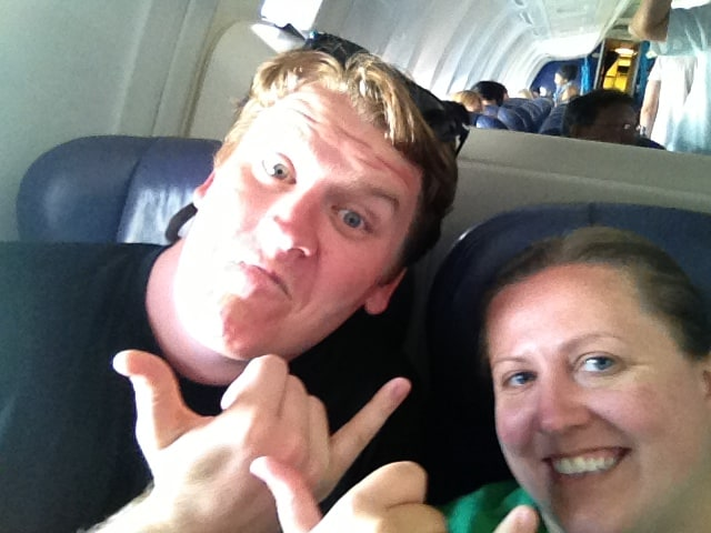 josh and liz pose in their seats on a fligth ready to take off wearing t-shirts and other comfy clothes for a long overnight flight to China