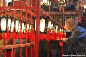 Tending to the lanterns in the Man Mo Temple