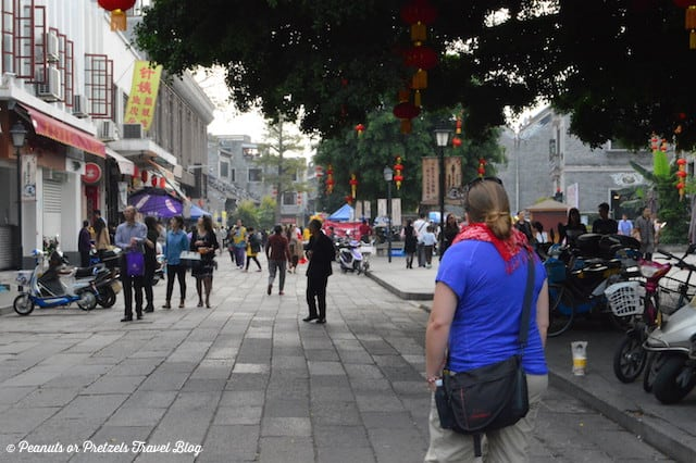 liz exploring shawan village in china with people on streets, shops and red lanterns hanging from trees