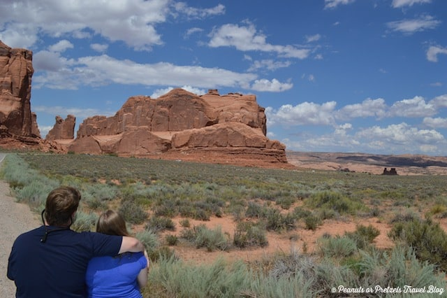 couple sitting on rock looking out at arches national park. Saved money to enjoy this trip with no worries.