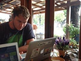 Josh working on the blog in a coffee shop in Thailand.