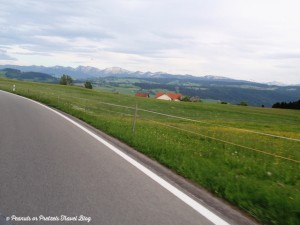 Driving rental car in northern Austria with stunning green fields, red roof buildings and alp mountains in background