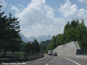 breathtaking scene driving a highway in Austria toward Italy with steep rocky mountains in background and pine trees around