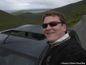 josh posing with our rental car in ireland looking out over the valley below