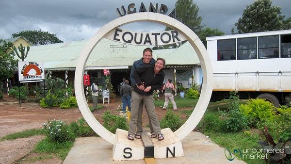 """Dan and Audrey standing at the equator line in Uganda."""