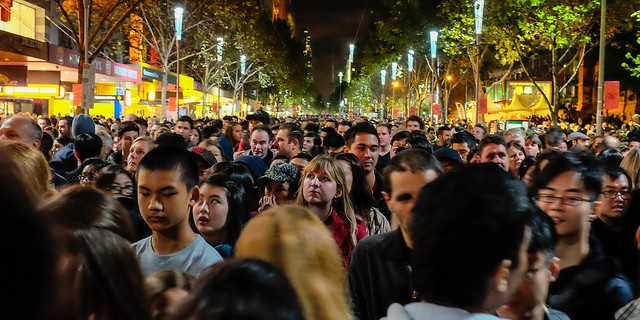 crowds of people in an Asia street at night celebrating a festival. Use your international travel checklist to remember holidays