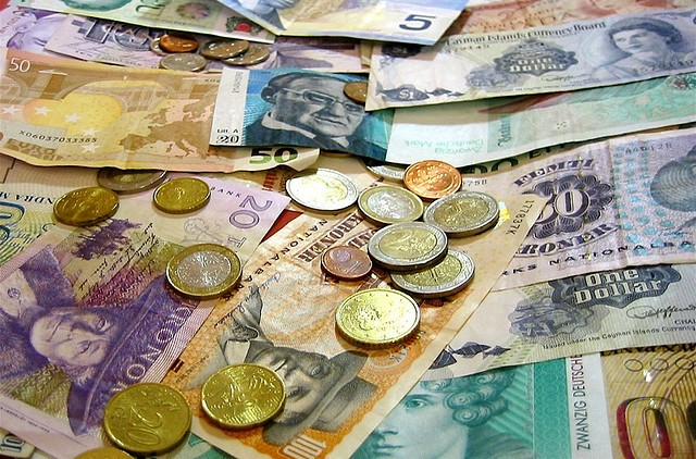 various colorful foreign currency and coins, be prepared with money by using the international travel checklist