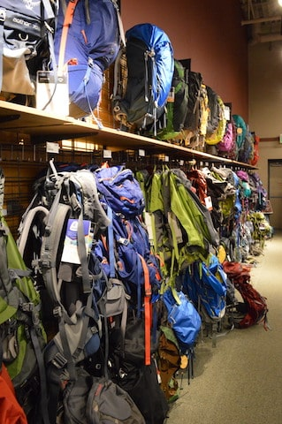 Wall of some of the best backpacks for travel at REI store to choose from