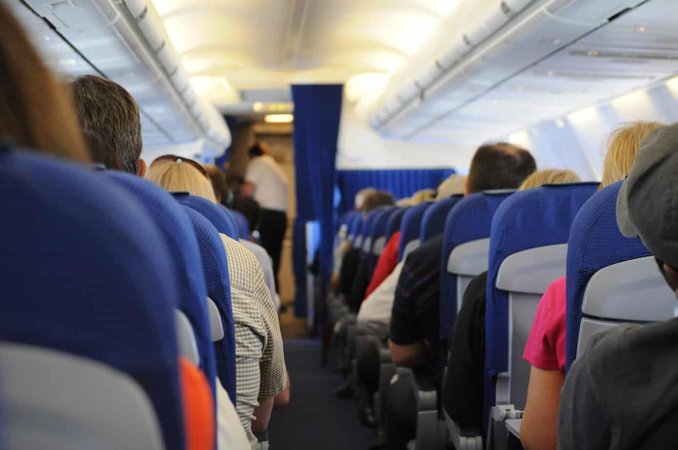 view looking down the aisle of an airplane facing the front, all wearing different clothes