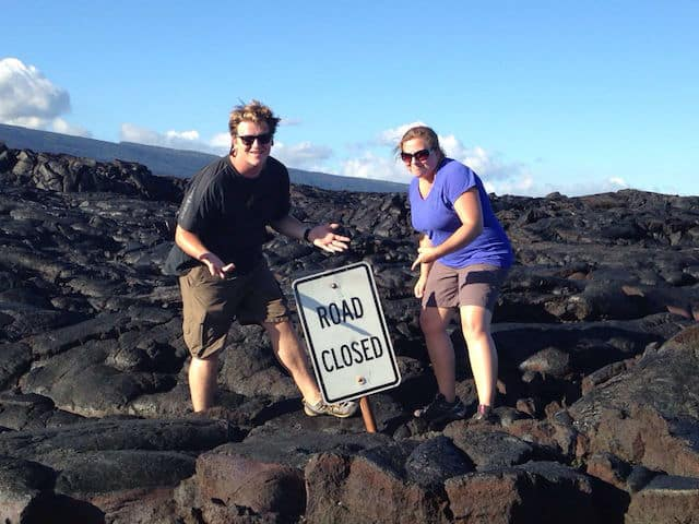 josh and liz standing on hardened lava rock in hawaii that swallowed a road sign! The road is closed, apparently - haha!
