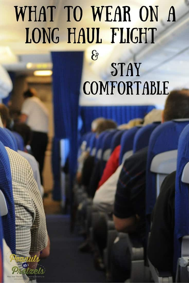 pinterest image for what to wear on a long flight with people on an airplane looking down the aisle