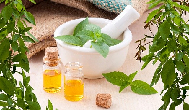 bowl herbs and bottles of essential oils for hot spring bath