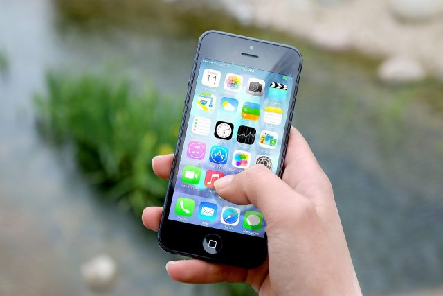 holding a smartphone with apps for travel