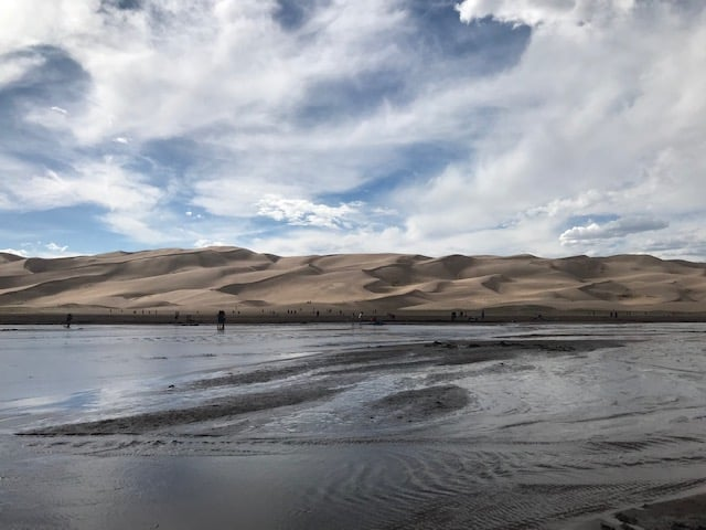 Photo of the Medano Creek, a seasonal creek at the foot of the Great Sand Dunes National Park - you can see the sand dunes in the distance across the creek with people wading through it.