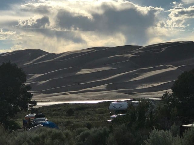 View of and RV and campsites at the Pinon Flats Campground inside the Great Sand Dunes National Park - great views behind the sites to the large dunes in the background.