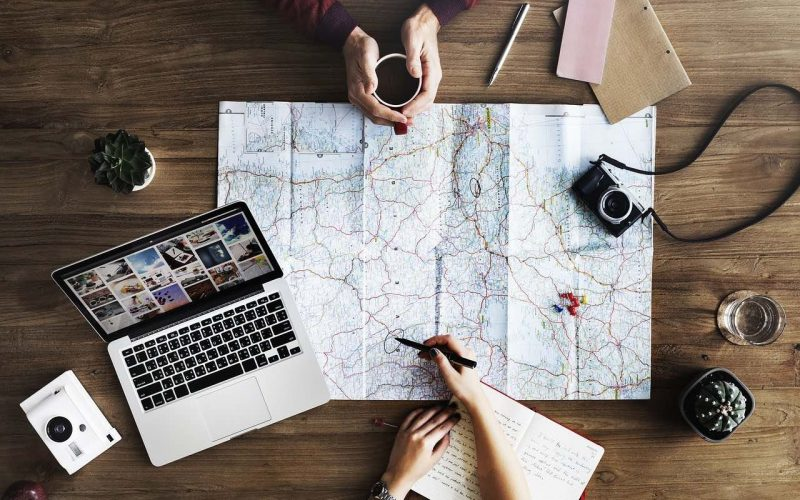 how to plan a trip table with map, computer, notes and 2 people's hands drawing on a map