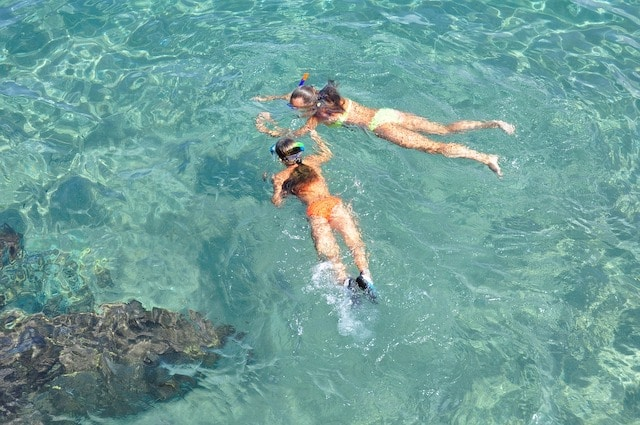 two girls snorkeling on top of crystal water