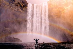 standing under waterfall and rainbow inspiring vacation quotes